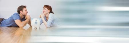 Digitale composiet van Gelukkige paar liggend op de vloer met een spaarvarken