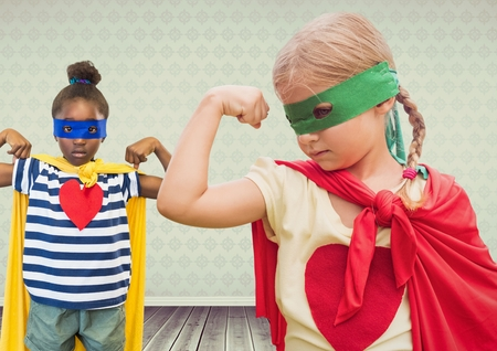 Digital composite of Superhero girl kids with blank room background Stock Photo