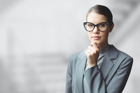 glass reflection: Digital composite of Business woman thinking against grey blurred background