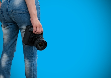 Digital composite of WOman holding camera in front of blue background Reklamní fotografie