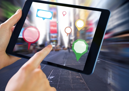 Digital composite of Holding tablet and City with colorful marker location pointers Stock Photo
