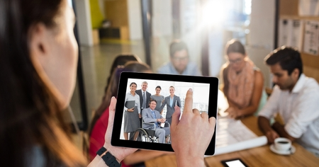 Digital composite of Female executive video conferencing with colleagues in office Stock Photo