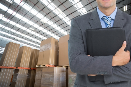 carboard box: Digital composite of man in suit in warehouse