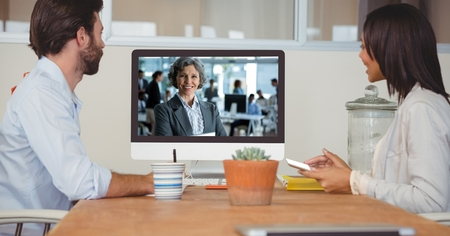 Digital composite of Business people video conferencing with colleague on computer