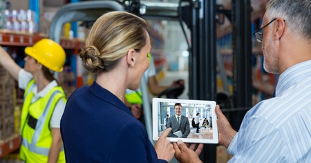 businesswear: Digital composite of Business people video conferencing in warehouse