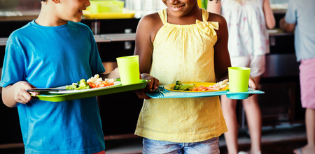 Smiling children holding food tray in canteen at school