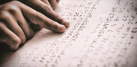 Cropped image of child using braille to read book at school