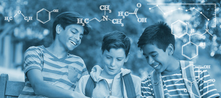 Digital image of chemical formulas against school kids using digital tablet on bench Stock Photo