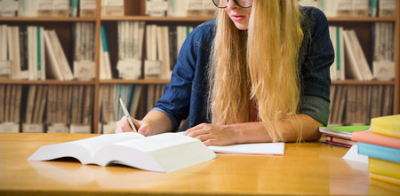 higher intelligence: Student studying in the library  against various multi colored books on shelf Stock Photo