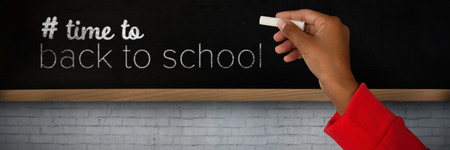 Cropped image of girl with hand raised holding chalk against blackboard on wall