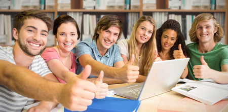 College students gesturing thumbs up in library against various multi colored books on shelf