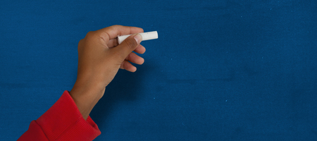 Cropped image of girl with hand raised holding chalk against navy blue Stock Photo