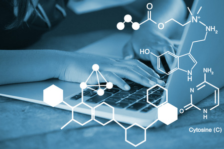 cytosine: Digitally generated image of chemical structure against schoolgirl using laptop against blackboard in classroom Stock Photo