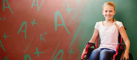 Girl sitting in wheelchair in school corridor against green chalkboard Stock Photo