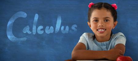 Smiling girl sitting at desk against blue background