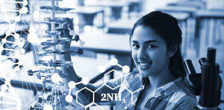DNA helix structure against white background against portrait of happy schoolgirl experimenting molecule model in laboratory