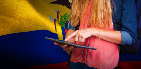 Student using tablet in library  against digitally generated ecuador national flag