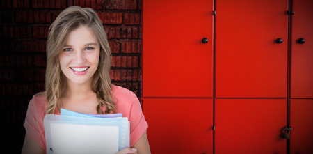 Smiling hipster holding notebook  against closed orange lockers against brick wall