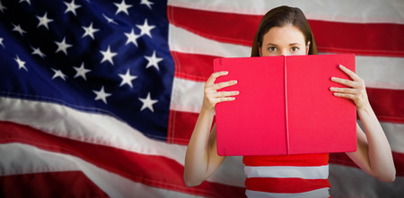 Student holding book over face against close-up of an flag Stock Photo
