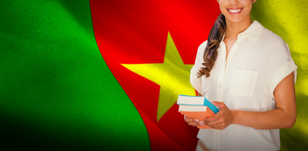 Happy student against digitally generated cameroon national flag Stock Photo