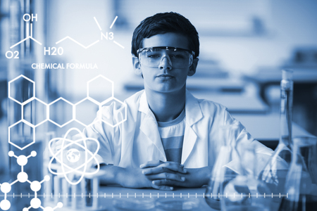 Graphic image of chemical formulas against portrait of schoolboy sitting in laboratory Stock Photo