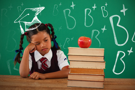thoughtful: B plus doodle against unhappy schoolgirl looking at books stack and apple against chalkboard Stock Photo