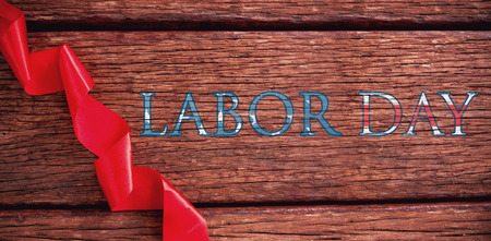 Poster of  labor day text against red ribbon on wooden table Stock Photo