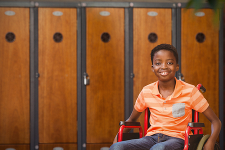 Portrait of boy sitting in wheelchair at library against close-up of brown lockers