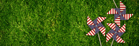 3D image of pinwheel toy with American flag pattern against full frame shot of grassy field