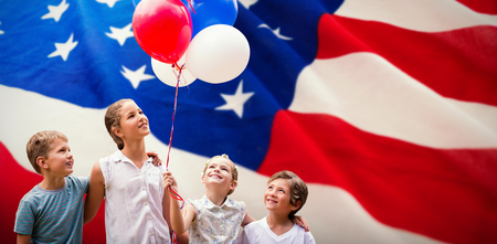 Girl with friends holding colorful balloons against american flag with stars and stripes
