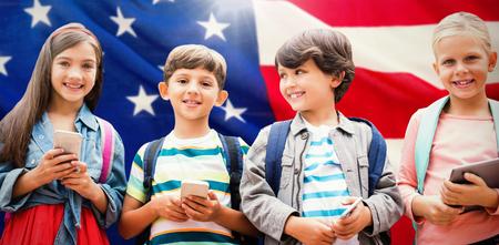 Portrait of children holding mobile phones against close-up of us flag