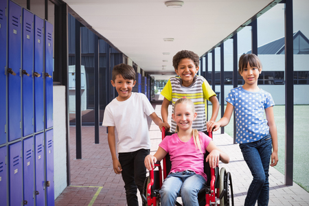 Cute disabled pupil smiling at camera with her friends against empty corridor at school
