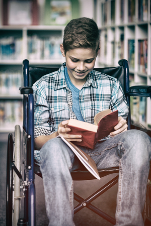 higher intelligence: Disabled schoolboy reading book in library at school