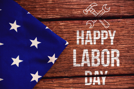 cytosine: Digital composite image of happy labor day text with tools against american flag on a wooden table Stock Photo