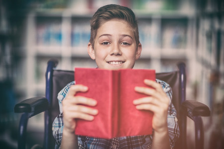 cytosine: Portrait of disabled schoolboy holding book in library at school