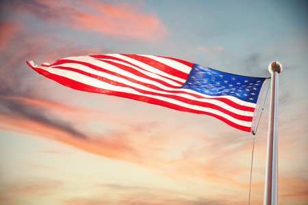 American flag waving over white background against full frame shot of sky Stock Photo