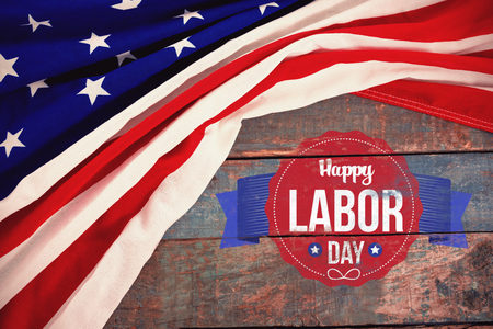 Happy labor day text in banner against american flag on a wooden table Stock Photo