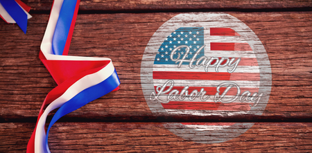 Happy labor day badge against red white and blue ribbons on table Stock Photo