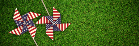 cytosine: 3D image composite of pinwheel with American flag pattern against full frame shot of grassy field