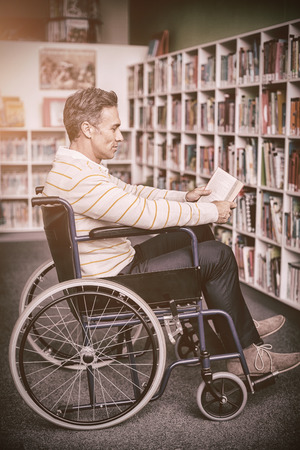 higher intelligence: Attentive disabled school teacher reading book in library at school Stock Photo