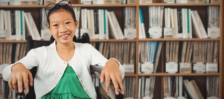 higher intelligence: Young girl smiling while sitting on wheelchair against various multi colored books on shelf