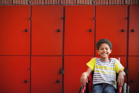 Cute disabled pupil smiling at camera in hall against close-up of orange lockers Stock Photo