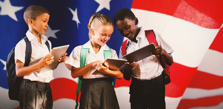 Students in uniforms using digital tablets against american flag with stripes and stars