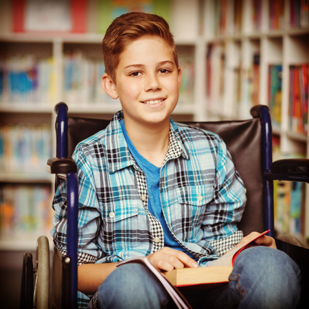 higher intelligence: Portrait of disabled schoolboy holding book in library at school