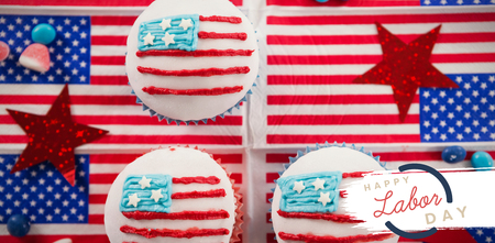Digital composite image of happy labor day text with blue outline against cupcakes on american flags