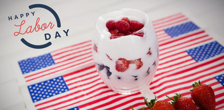 Digital composite image of happy labor day text with blue outline against dessert in glass on american flags