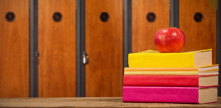 Apple with books on wooden table against close-up of brown lockers Stock Photo