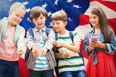 Boy with friends using mobile phone against american flag with stars and stripes