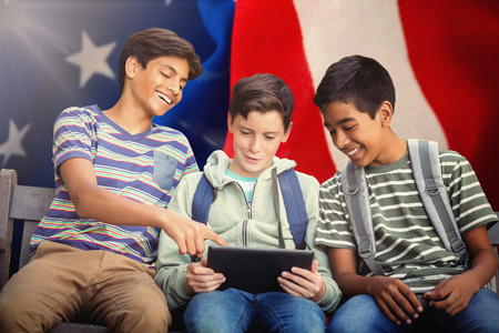 Boy with friends using digital tablet on bench against crumbled american flag