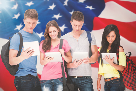 Students with backpacks looking at their tablets against american flag with stars and stripes